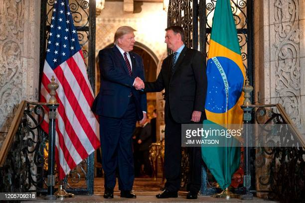 US President Donald Trump shakes hands with Brazilian President Jair Bolsonaro during a diner at MaraLago in Palm Beach Florida on March 7 2020
