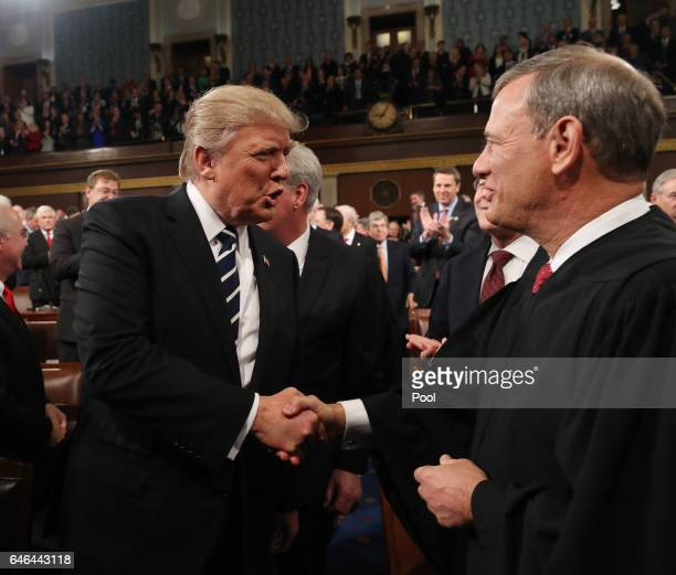President Donald Trump shakes hands with Chief Justice John Roberts as he arrives to deliver an address to a joint session of the U.S. Congress on...