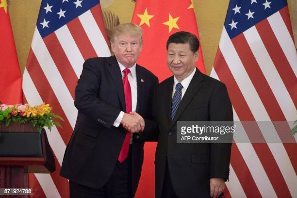 US President Donald Trump shakes hands with China's President Xi Jinping during a press conference at the Great Hall of the People in Beijing on...