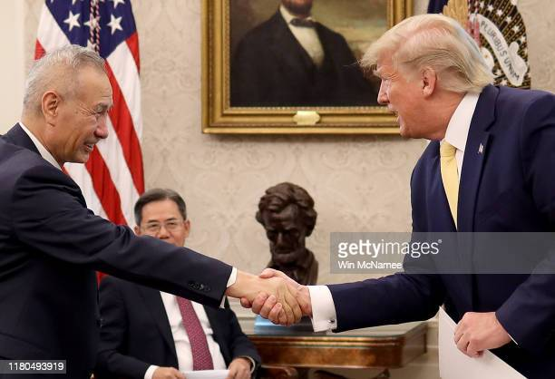 """President Donald Trump shakes hands with Chinese Vice Premier Liu He after announcing a """"phase one"""" trade agreement with China in the Oval Office at..."""