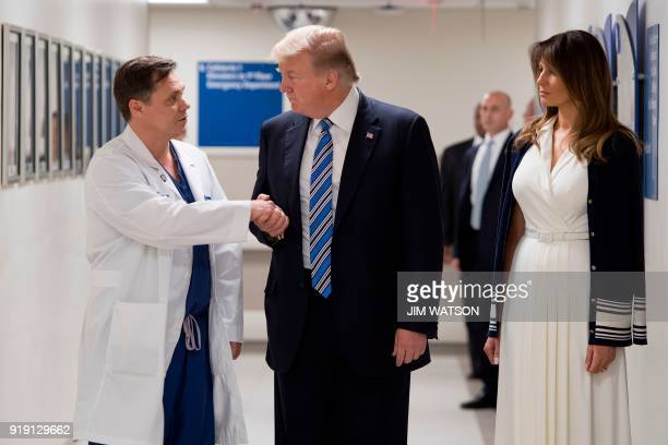 US President Donald Trump shakes hands with doctor Igor Nichiporenko beside First Lady Melania Trump while visiting first responders at Broward...