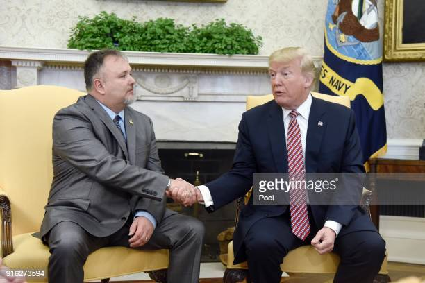 US President Donald Trump shakes hands with Don Bouvet who has been battling cancer in the Oval Office of the White House February 9 2018 in...