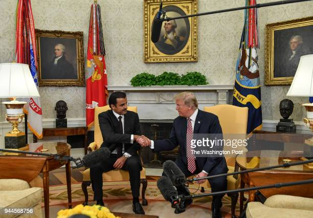 President Donald Trump shakes hands with Emir of Qatar Sheikh Tamim bin Hamad Al Thani during a meeting in the Oval Office at the White House on...
