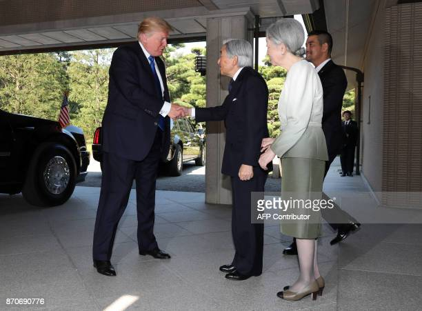 US President Donald Trump shakes hands with Emperor Akihito as Empress Michiko looks on at the Imperial Palace in Tokyo on November 6 2017 President...