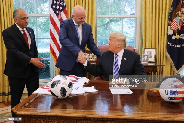 S President Donald Trump shakes hands with FIFA President Gianni Infantino and US Soccer President Carlos Cordeiro in the Oval Office at the White...