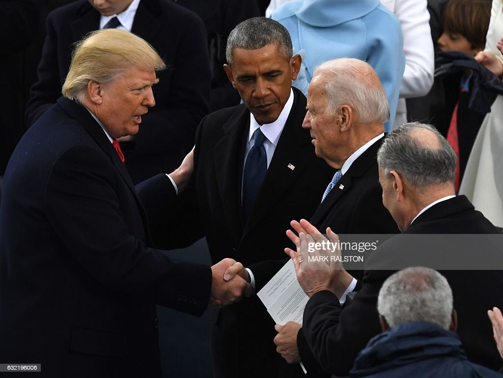 US President Donald Trump (L) shakes hands with former US President Barack Obama (C) and former vice-President Joe Biden after being sworn in as President on January 20, 2017 at the US Capitol in Washington, DC. / AFP / Mark RALSTON