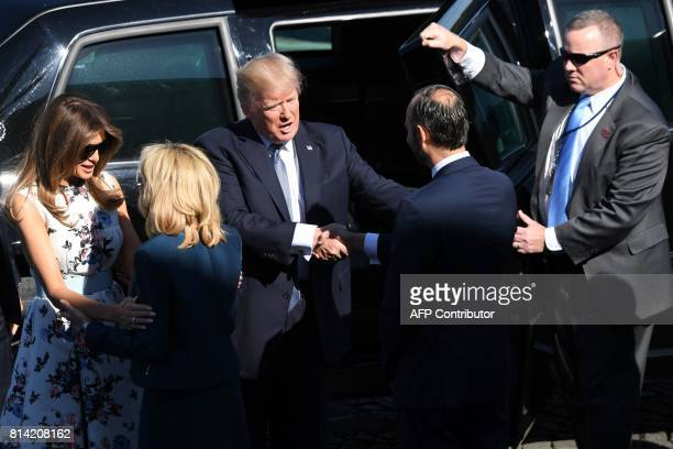 US President Donald Trump shakes hands with French Prime Minister Edouard Philippe next to Brigitte Macron wife of French President greeting US First...