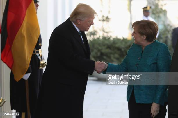 S President Donald Trump shakes hands with German Chancellor Angela Merkel as she arrives to the White House on March 17 2017 in Washington DC