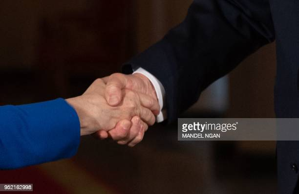 US President Donald Trump shakes hands with Germany's Chancellor Angela Merkel during a joint press conference in the East Room of the White House on...