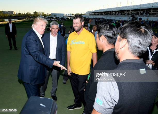President Donald Trump shakes hands with Hideki Matsuyama of Japan and the International Team as Marc Leishman looks on after the US Team defeated...