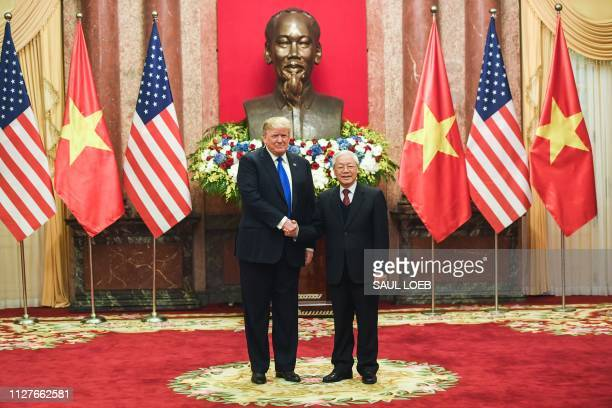 US President Donald Trump shakes hands with his Vietnamese counterpart Nguyen Phu Trong before a meeting at the Presidential Palace in Hanoi on...
