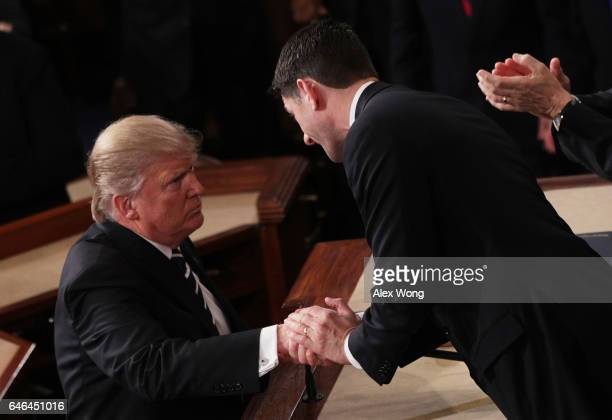 S President Donald Trump shakes hands with House Speaker Rep Paul Ryan after addressing a joint session of the US Congress on February 28 2017 in the...