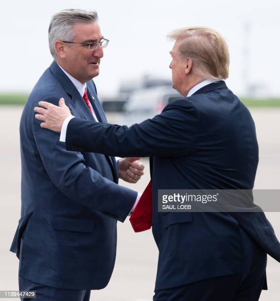 President Donald Trump shakes hands with Indiana Governor Eric Holcomb upon arrival at Indianapolis International Airport in Indiana, April 26, 2019....