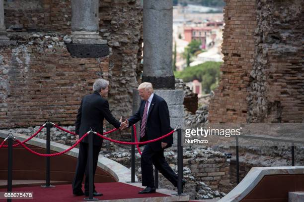 US President Donald Trump shakes hands with Italian Prime Minister Paolo Gentiloni as he arrives at the Ancient Theatre of Taormina ahead the G7...