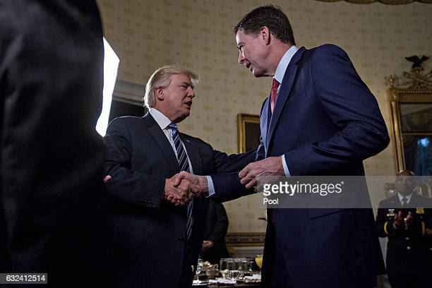 S President Donald Trump shakes hands with James Comey director of the Federal Bureau of Investigation during an Inaugural Law Enforcement Officers...
