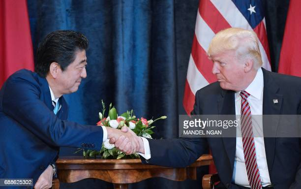 President Donald Trump shakes hands with Japanese Prime Minister Shinzo Abe during a bilateral meeting at the Villa Diodoro on the sidelines of the...