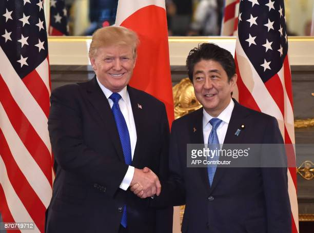 US President Donald Trump shakes hands with Japanese Prime Minister Shinzo Abe before a summit meeting at Akasaka Palace in Tokyo on November 6 2017...