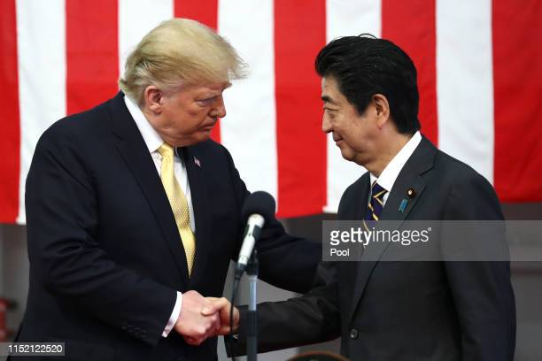 President Donald Trump shakes hands with Japan's Prime Minister Shinzo Abe during delivering a speech to Japanese and U.S. Troops as they aboard...
