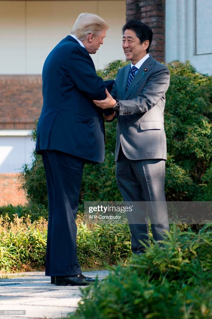 US President Donald Trump (L) shakes hands with Japan's Prime Minister Shinzo Abe (R) as he arrives for a luncheon at the Kasumigaseki Country Club Golf Course in Kawagoe, Saitama prefecture, outside Tokyo on November 5, 2017. Trump touched down in Japan on November 5, kicking off the first leg of a high-stakes Asia tour set to be dominated by soaring tensions with nuclear-armed North Korea. /
