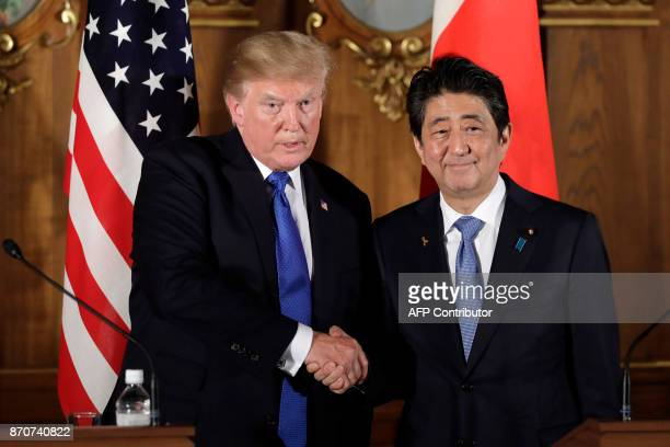 President Donald Trump shakes hands with Japan's Prime Minister Shinzo Abe during a news conference at Akasaka Palace in Tokyo on November 6 2017 /...