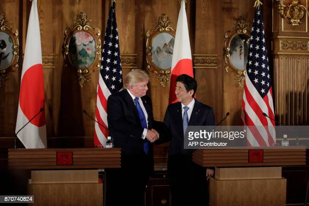 US President Donald Trump shakes hands with Japan's Prime Minister Shinzo Abe during a news conference at Akasaka Palace in Tokyo on November 6 2017...
