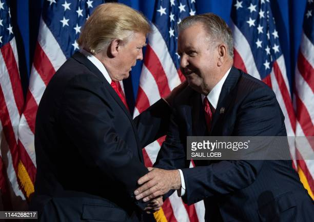 US President Donald Trump shakes hands with John Smaby President of the National Association of Realtors as Trump arrives to speak during the NAR...