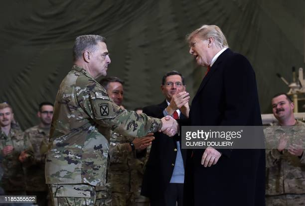 US President Donald Trump shakes hands with Joint Chiefs Chairman General Mark Milley before addressing the troops at Bagram Air Field during a...
