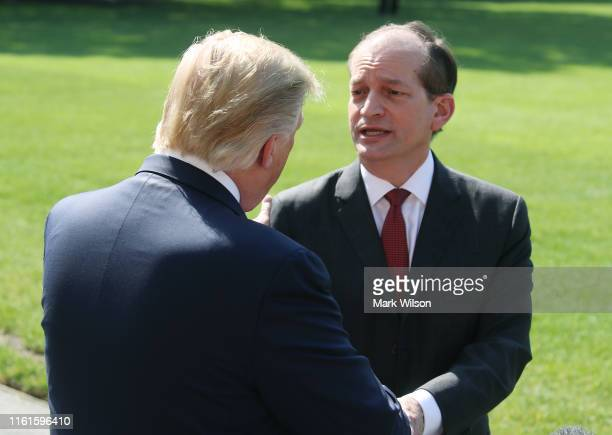 S President Donald Trump shakes hands with Labor Secretary Alex Acosta after talking to the media about his resignation at the White House on July 12...