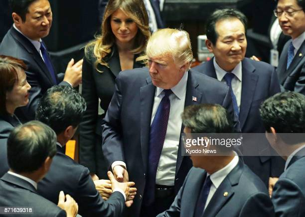 US President Donald Trump shakes hands with lawmakers after delivering a speech at South Korea's parliament in Seoul on Nov 8 2017 His speech...