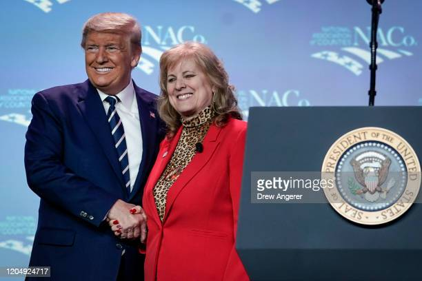 S President Donald Trump shakes hands with National Association of Counties President Mary Ann Borgeson before addressing the NACo conference at the...