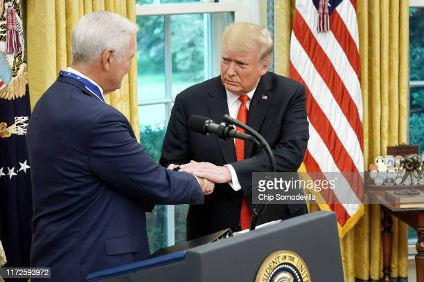 S President Donald Trump shakes hands with National Basket Ball Hall of Fame inductee Jerry West after presenting him with the Presidential Medal of...