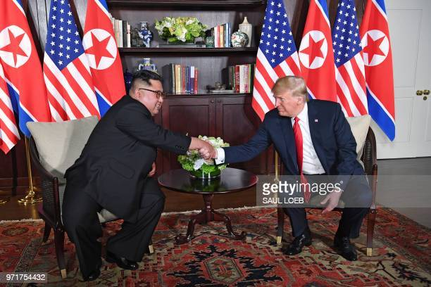President Donald Trump shakes hands with North Korea's leader Kim Jong Un as they sit down for their historic US-North Korea summit, at the Capella...