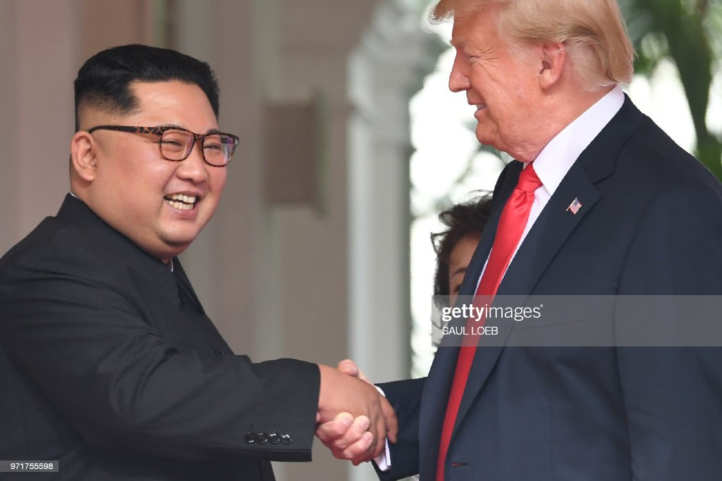 President Donald Trump (R) shakes hands with North Korea's leader Kim Jong Un as they meet at the start of their historic US-North Korea summit, at the Capella Hotel on Sentosa island in Singapore on June 12, 2018. - Donald Trump and Kim Jong Un have become on June 12 the first sitting US and North Korean leaders to meet, shake hands and negotiate to end a decades-old nuclear stand-off.