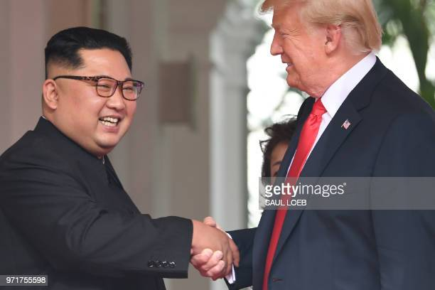 President Donald Trump shakes hands with North Korea's leader Kim Jong Un as they meet at the start of their historic USNorth Korea summit at the...