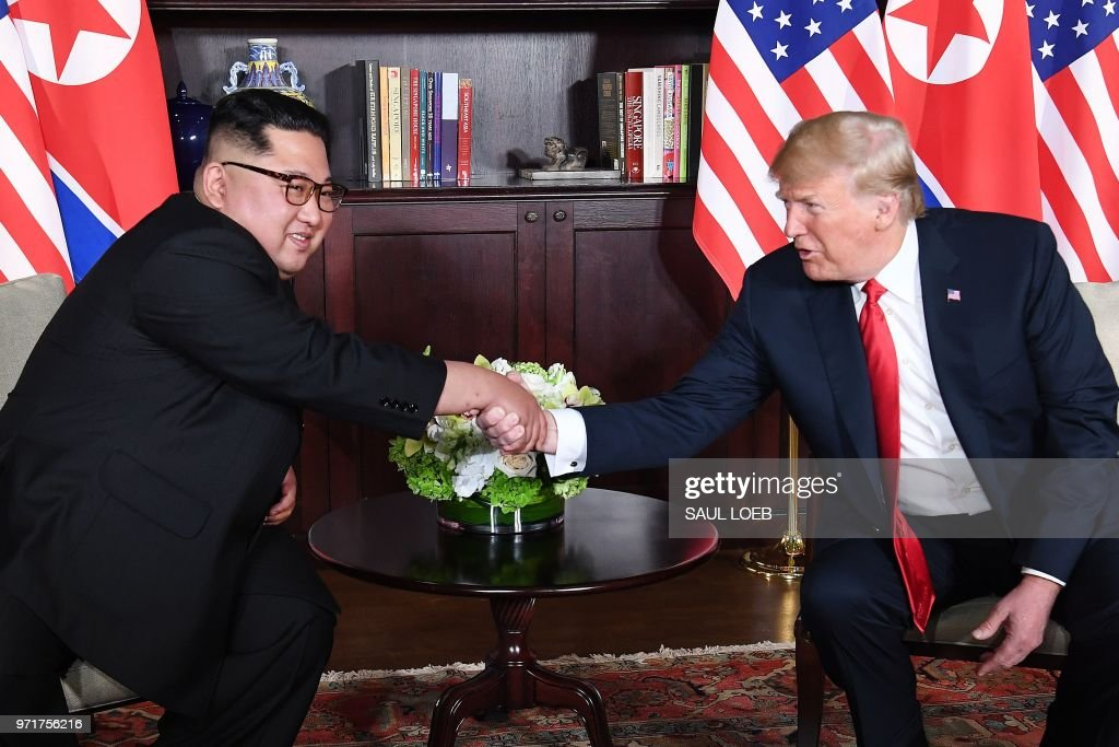 President Donald Trump (R) shakes hands with North Korea's leader Kim Jong Un (L) as they sit down for their historic US-North Korea summit, at the Capella Hotel on Sentosa island in Singapore on June 12, 2018. - Donald Trump and Kim Jong Un have become on June 12 the first sitting US and North Korean leaders to meet, shake hands and negotiate to end a decades-old nuclear stand-off.
