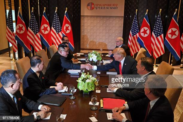 US President Donald Trump shakes hands with North Korea's leader Kim Jong Un as they sit down with their respective delegations for the USNorth Korea...