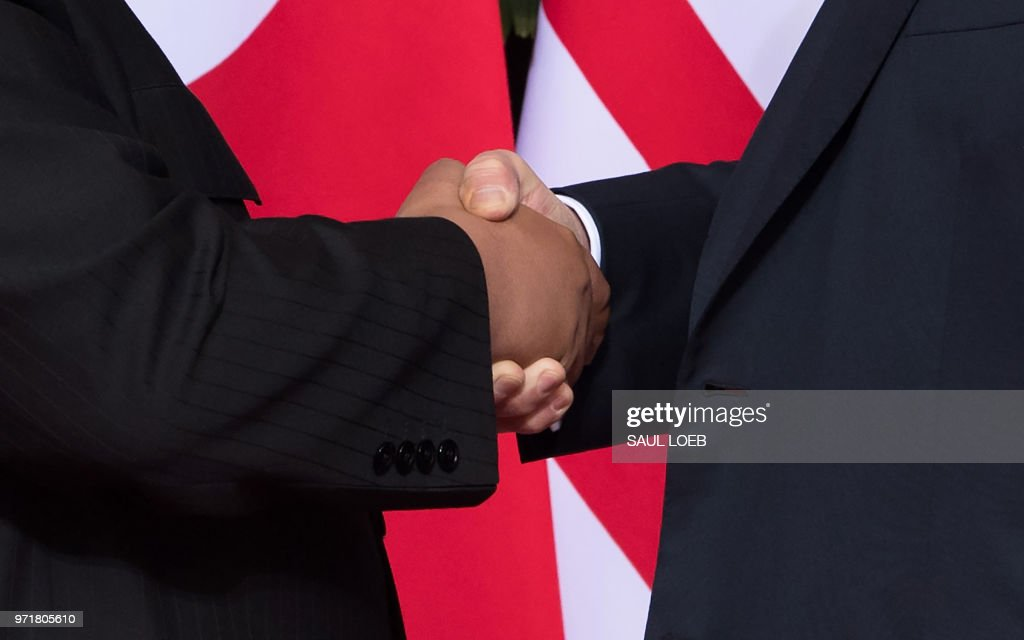 President Donald Trump (R) shakes hands with North Korea's leader Kim Jong Un (L) at the start of their historic US-North Korea summit, at the Capella Hotel on Sentosa island in Singapore on June 12, 2018. - Donald Trump and Kim Jong Un became on June 12 the first sitting US and North Korean leaders to meet, shake hands and negotiate to end a decades-old nuclear stand-off.