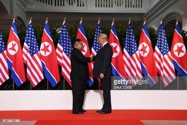 US President Donald Trump shakes hands with North Korea's leader Kim Jong Un at the start of their historic USNorth Korea summit at the Capella Hotel...