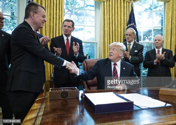 US President Donald Trump shakes hands with Pastor Andrew Brunson after signing the America's Water Infrastructure Act of 2018 in the Oval Office of...