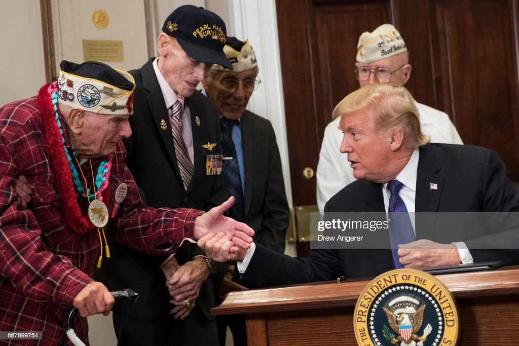U.S. President Donald Trump shakes hands with Pearl Harbor survivor Larry Parry (L) after signing a proclamation for National Pearl Harbor Remembrance Day, in the Roosevelt Room of the White House, December 7, 2017 in Washington, DC. Thursday is the 76th anniversary of the attacks against the Hawaii naval base.