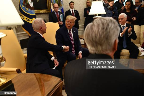 US President Donald Trump shakes hands with Rep Jeff Van Drew DNJ as US Vice President Mike Pence and other cabinet members look on in the Oval...