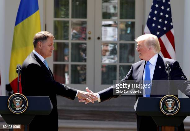 S President Donald Trump shakes hands with Romanian President Klaus Iohannis as they hold a joint news conference in the Rose Garden at the White...