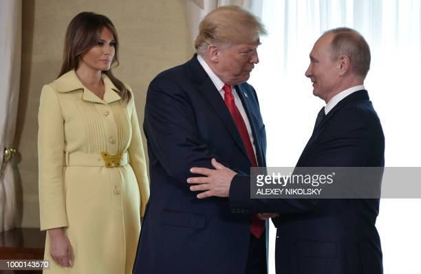 US President Donald Trump shakes hands with Russia's President Vladimir Putin next to US First Lady Melania Trump ahead a meeting in Helsinki on July...