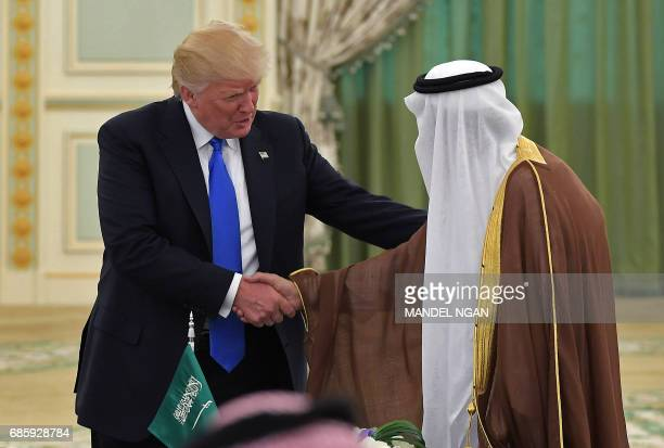 US President Donald Trump shakes hands with Saudi Arabia's King Salman bin Abdulaziz alSaud during a signing ceremony at the Saudi Royal Court in...