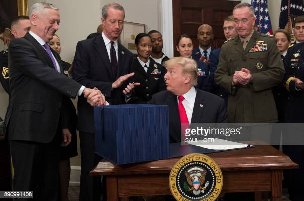 US President Donald Trump shakes hands with Secretary of Defense Jim Mattis after signing HR 2810 National Defense Authorization Act for Fiscal Year...