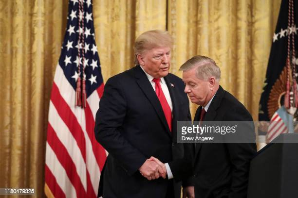 President Donald Trump shakes hands with Sen. Lindsey Graham during an event about judicial confirmations in the East Room of the White House on...