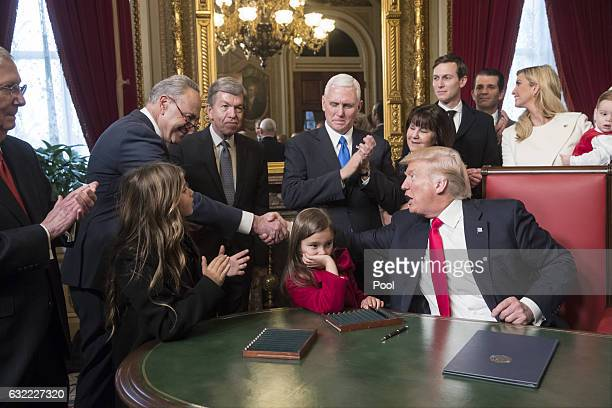 President Donald Trump shakes hands with Senate Minority Leader Chuck Schumer DNY as he is joined by the Congressional leadership and his family...