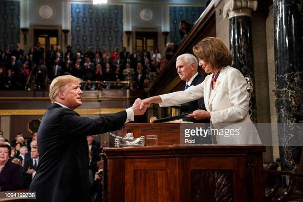 S President Donald Trump shakes hands with Speaker of the House Nancy Pelosi while joined by Vice President Mike Pence before delivering the State of...