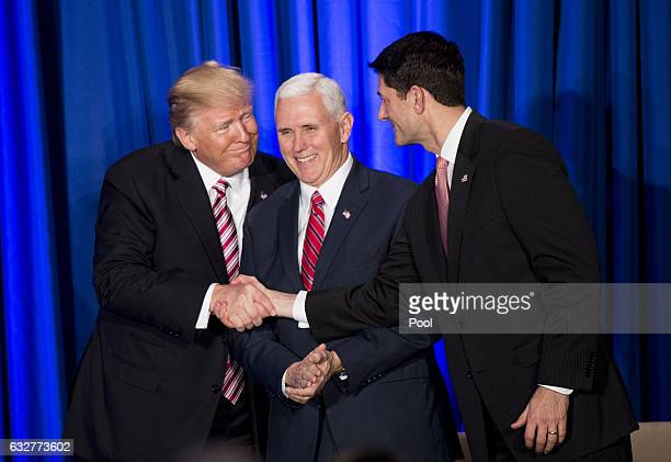 S President Donald Trump shakes hands with Speaker of the House Paul Ryan while Vice President Mike Pence looks on during a luncheon at the Congress...