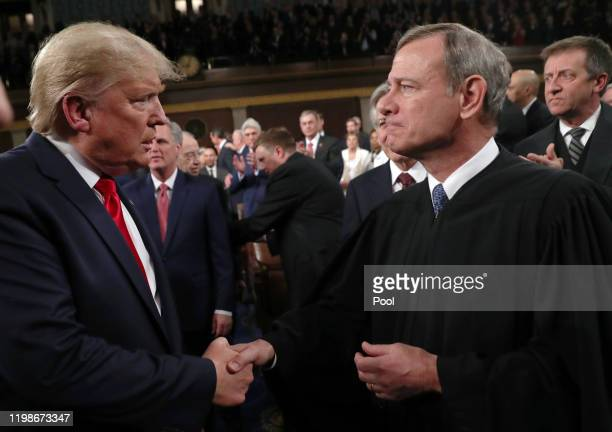 President Donald Trump shakes hands with Supreme Court Chief Justice John Roberts before the State of the Union address in the House chamber on...